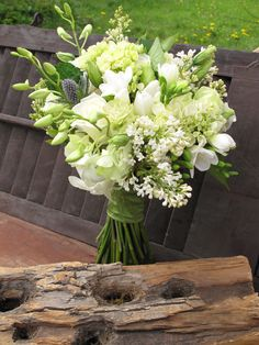 Spring bridal bouquet of white lilacs, freesia, roses, orchids, hydrangea, lisianthus and thistle.