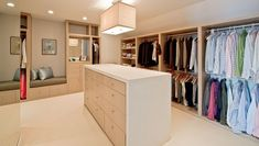 This modern walk in closet has an excellent combination of colors and closed & open storage. The space is fairly large further enhanced by one full-height mirror wall, giving you lots of room for storage. Clothes are mostly displayed on open hanging racks and shelves, while more intimate items and other accessories are kept in the drawers. It has a large island counter with plain white solid surface top and sides, and has light beech wood laminates for its drawers.