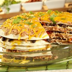 Black beans and pinto beans are flavored with Pace® Picante Sauce and seasonings to make separate and delicious bean mixtures, which are then layered with flour tortillas and Cheddar cheese, and baked until hot, cut into wedges and served.