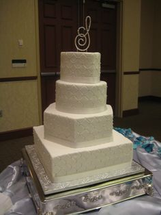 4-tier mixed shape wedding cake. Includes heart, round, hexagon and square tiers.