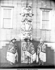 Three men of the Kogwanton clan in ceremonial regalia standing around the Panting Wolf carving; 1904 potlatch in Sitka. :: Alaska State Library-Historical Collections
