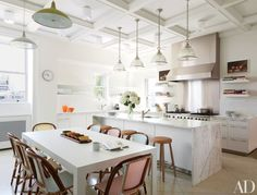 Shelton, Mindel & Assoc. gave this New York City apartment a makeover, suspending holophane light fixtures by Ann-Morris Antiques above the kitchen's marble island. Bistro chairs by TK Collections surrounding a Bulthaup table provide additional seating.