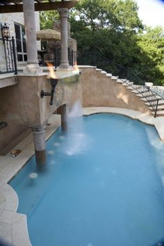 Hot tub on top spilling over into pool below with a pool bar