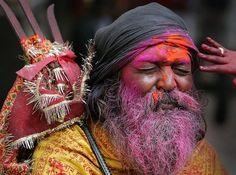 """A Sadhu, or Hindu holy man reacts after a boy, only hands seen, rubs colored powder on his face during """"Holi"""" celebrations at Kamakhya temple in Gauhati, India, Saturday, March 3, 2007. Holi, the Hindu festival of colors, also heralds the coming of spring. (AP Photo/Anupam Nath)"""