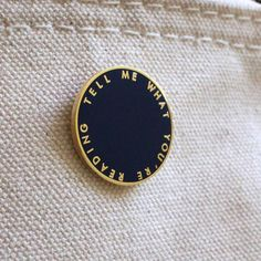 "Just in, new enamel-and-metal pins in two styles: the conversation-starting ""TELL ME WHAT YOU'RE READING"" in Navy Blue and Gold, and our classic handwritten ""Book/Shop"" logo in White & Gold. 1"" diamet"