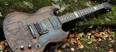 Viking themed guitar on a Gibson SG featuring a detailed carving of Odin with his two ravens Huginn and Muninn and at his feet his two wolves Geri and Freki.