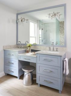 West Elm Martini Side Table sits beneath a blue dual washstand fitted with a drop down makeup vanity and accented with polished nickel pulls and a gray stone countertop.