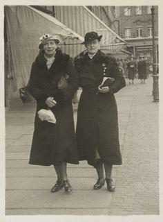 Princesa Tatiana Constantinovna e Princesa Vera Constantinovna, em 1935. Elas estão de pé juntas em uma rua, com a Princesa Vera para a direita. Ambas estão vestindo casacos longos escuros e chapéus, e estão carregando bolsas e pacotes.