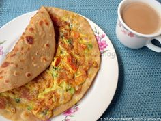 Anda Paratha - Desi breakfast dish of fried flatbread + omelette with vegetables and spices. Cup of chai shown on side.  Often had this growing up, makes me miss home.