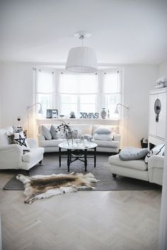 Gorgeus white living room with hide rug on the floor and with christmas decorations.