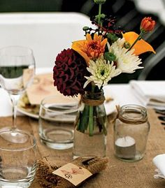 Keep the decor simple with masons jars, tealights and rustic flowers for a centerpiece setup