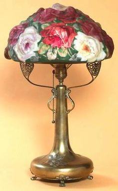 """lighting, Massachusetts, A signed Pairpoint Puffy rose table lamp having blown out cabbage roses in three colors over a multi-colored leafy stemmed background with orange and yellow accents, signed on the inner rim """"Pairpoint Corperation"""" in gold letters, the conforming three-footed brass base with inlaid silver floral designs, marked Pairpoint manufacturing Co, impressed in a diamond, quadrupleplate #3033. Circa 1900-1925"""