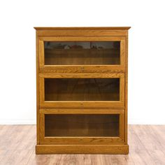 This lawyer's bookcase is featured in a solid wood with a glossy oak finish. This farmhouse style bookshelf has 3 shelves w/ lockable glass doors, simple straight sides, and crown moulding. Perfect for the home office! #countryfarmhouse #storage #bookcase&shelving #sandiegovintage #vintagefurniture