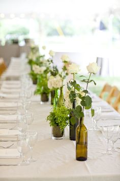 Wine bottles as vases for centerpieces.    Photo:  Mel & Co.