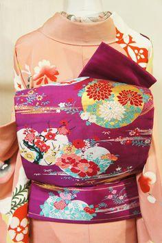 こっくりと深い紫色地に、牡丹や梅、菊花や橘、撫子など四季の草花で彩られた橘文様が風情をさそうアンティークムードただよう名古屋帯です。