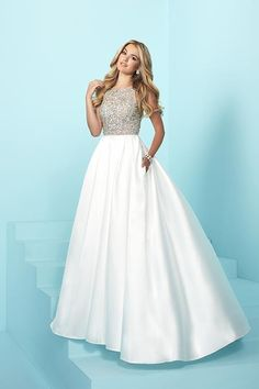 Jacquelin Bridals Canada - 16253 - Prom - Make an unforgettable entrance in this sophisticated gown. The empire bodice has a high neckline and is adorned with hand-sewn beadwork. A box pleated skirt of silky mikado has a sweep train and pockets. The v-back closes with a center zipper.