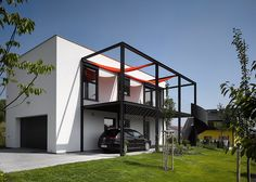 house for a racing driver, Czech studio Stempel & Tesar has shifted the living spaces upstairs to make room for a car workshop below Facade Design, Architecture Design, House Design, Dezeen Architecture, Retail Facade, Car Workshop, Balcony Railing Design, House Extensions, Car Shop