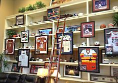 Full of sports memorabilia, this wall at our store would be perfect for any sports aficionado! #ManCave #GFToday | Houston TX | Gallery Furniture |