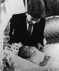 Prince Charles admiring his new baby brother, Prince Andrew in March 1960