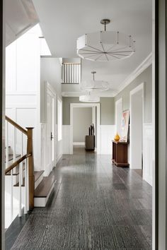 """Don't use the same shade room to room. Bohn chose a darker shade of gray, Sherwin Williams Dovetail, for the hallway, which runs the length of the house. """"All the grays in the adjoining rooms are lighter,"""" says Bohn, """"so you get a pleasant surprise—a subtle sense of increased illumination—when you enter them."""" The hallway floor is tiled in dark greenish-gray marble with a distinctive pattern that adds a little drama. The staircase has walnut treads and a red-oak bannister that, along with…"""