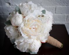 This soft and romantic ivory peony bouquet is a wonderful bridesmaids or flower girl bouquet. Six petite ivory peonies are tied with rustic soft