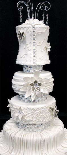 Four-tiered wedding cake features pearl-dusted fondant wrap and is embellished with rhinestone buttons and loops, hand-strung crystal drops, aluminum jewelry wire with hand-tied crystal drops and a stylized lotus flower