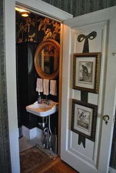 art of monkeys on the door on painted ribbon, black wainscoating?, gold mirror, wall paper, rug, linens ~ charming