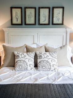 Framed floral prints are displayed above a wood panel headboard painted in white and lightly distressed.