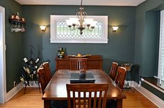 Dining room with leaded glass window, blue walls, wine bottle tree, wood dining table and chairs set.