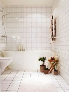 stacked white tile, glass partition, free standing tub, toilet off the floor, bright, clean, bright. add built in storage within the shower space and it's perfect!