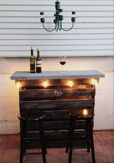 DIY Patio Pallet Bar: Screw together 2 pallets, spray paint your fav color, pick out pavers for counter top, glue pavers to pallets with construction adhesive, staple cute patio lights below counter. You're DONE! More