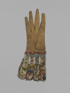 Glove Date:     ca. 1600 Culture:     British Medium:     Leather, silk and metal thread on cloth, sequins and lace Dimensions:     L. 14 x W. 5 1/4 inches (35.6 x 13.3 cm)