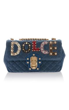 "Leave it to designers Domenico Dolce and Stefano Gabbana to take your closet staples to a new, energized level. This suede bag features a gold chain and red leather top handle, accented with a multicolor crystal ""DG"" monogram. Play up this fun-loving purse with a bright summer dress a pair of equally as colorful slides."