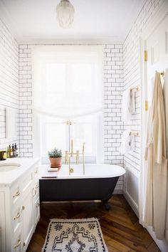 Brick walls black tub gold hardware white sink wooden floors tribal printed rug #summer #vibes #currentlycoveting