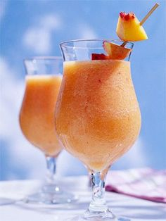 Summer Fruit Daiquiris ~ 3 cups pitted, peeled, and sliced fresh peaches, frozen (thawed), unsweetened peach slices, or fresh or frozen unsweetened, strawberries, 1/2 of a 12-ounce can frozen limeade or lemonade concentrate, thawed, 1/4 cup light rum or orange juice, 2 tablespoons powdered sugar, 2 to 3 cups ice cubes, Fresh peach chunks or small fresh strawberries (optional)