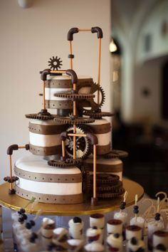 I love the way the gears look as if they might actually do something, instead of looking like they were just thrown at the cake.  I like the pieces removed from the round layers to allow for the gears to feel incorporated.