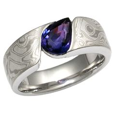 Mokume Wave Engagement Ring with Bicolor Sapphire - An organically shaped mokume band that is contoured to a variety of stone shapes. This engagement ring's stone is flush set to the band, which thickens toward the top of the finger to allow for the depth of the stone. - This handmade engagement ring is set with a pear shaped bicolor sapphire. Its band features inlaid White mokume gane.