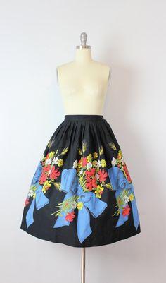 Vintage jaren 1950 zwarte katoenen rok met een print van de grens van boeketten van bloemen gebonden met grote blauwe bogen. Gestreepte taille