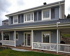 Dunkelblaue Fensterläden verstärken die Maus-Blau-Graue Farbe der Fassade. Weiße Verzierungen bilden einen tollen Kontrast.