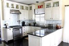 Dazzling U Shaped Kitchen Design Using Modular White Cabinets Combined With Black Granite Countertop Plus Hanging White Kitchen Storage As Well As Built In Appliances And Small Window With Valances Design. .