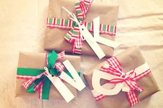 Christmas presents wrapped in brown packaging paper, ribbon, & white cut out initials for the tags