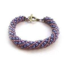 A Simple Russian Spiral Bracelet Hand Weaved Using Purple Coloured Gl Pearls And Bronze Seed Beads Finished With Antique Caps