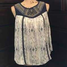 Xhilaration Boho Sleeveless embroidered Top! Xhilaration Boho Sleeveless embroidered Top! This is an adorable top in a navy blue and cream print with navy blue lace running down the front and a light pink, yellow and white stitching in a boho print on the front yoke of this top! The back has a triangle shaped opening below a small engraved round brass button closure at the neckline! This top will be your perfect summer go to top with a pair of capris on those warm summer days!  Xhilaration…