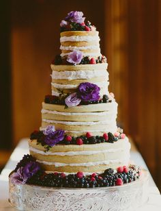 Naked cake with purple flowers + fruit