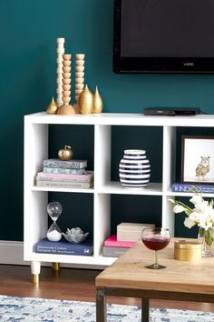 """Splurge on the double Ikea Kallax shelf (it's only $5 more), lay it on its side, and it becomes a clutter-busting television stand. """"When a TV is mounted on the wall, you need storage under it, period,"""" says Pregenzer. """"You don't want people to focus on the cable box, DVD cases, or gaming components. Storage allows you to keep all that ugliness at bay."""" Kallax shelving unit, $64.99; ikea.com."""