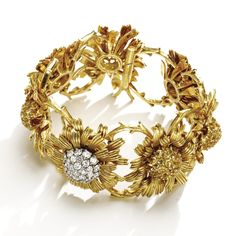 """18 KARAT GOLD, YELLOW BERYL AND DIAMOND """"DAHLIA"""" BRACELET-WATCH, SCHLUMBERGER FOR TIFFANY & CO., CIRCA 1959 Designed as a row of seven dahlias,thecentralflowerhead set with a bombé-cluster of round diamonds, opening to reveala circular watch dial, the remaining flowerheads set with clusters of round yellowberyls, movement by Movado, length 6¾ inches, dial and bracelet signed Tiffany, Schlumberger.With box signed Tiffany & Co."""