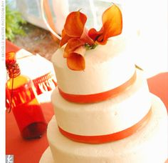 Each tier of the wedding cake was wrapped at the base in burnt orange ribbon, and the entire confection was topped with more burnt orange calla lilies.