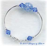 Designs by Debi Handmade Jewelry Blue Aloha Floral and Swarovski Crystal Sapphire Bicones Curved Tube Bracelet with a Silver Lobster Clasp $20