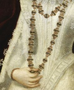 Portrait of a lady, half length, wearing a white richly embroidered dress and holding necklace, Detail. by follower of Alonso Sánchez Coello