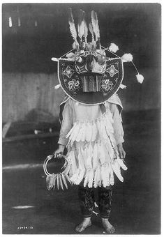 Title: Masked dancer–Cowichan Date Created/Published: c1913 June 16. Summary: Dancer wearing oversize mask, three rings of feathers in front of clothing, holding a rattle.